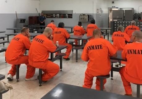 Inmates in facility cafeteria wearing orange uniforms.