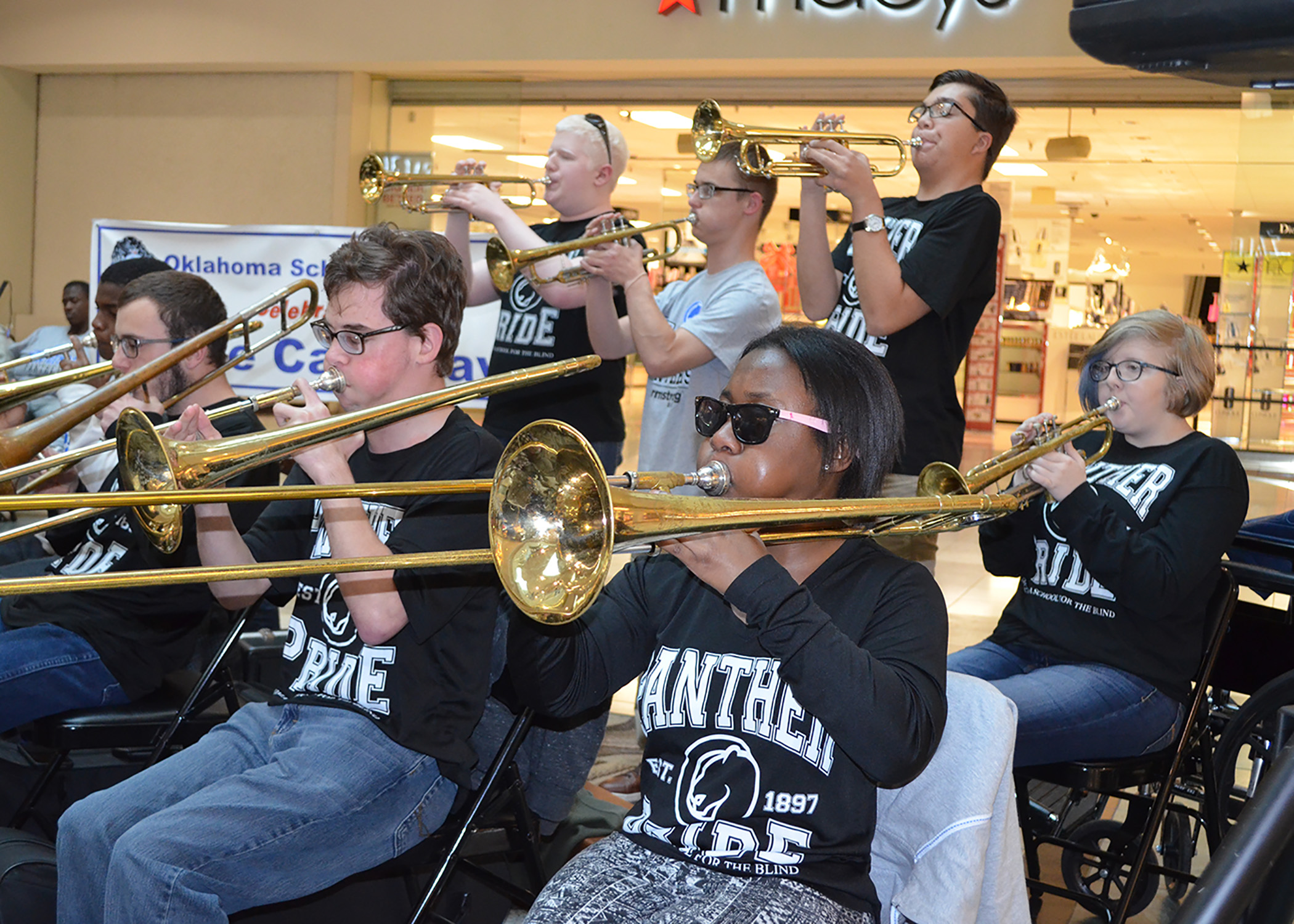 Students play trombones and trumpets in front of a mall store