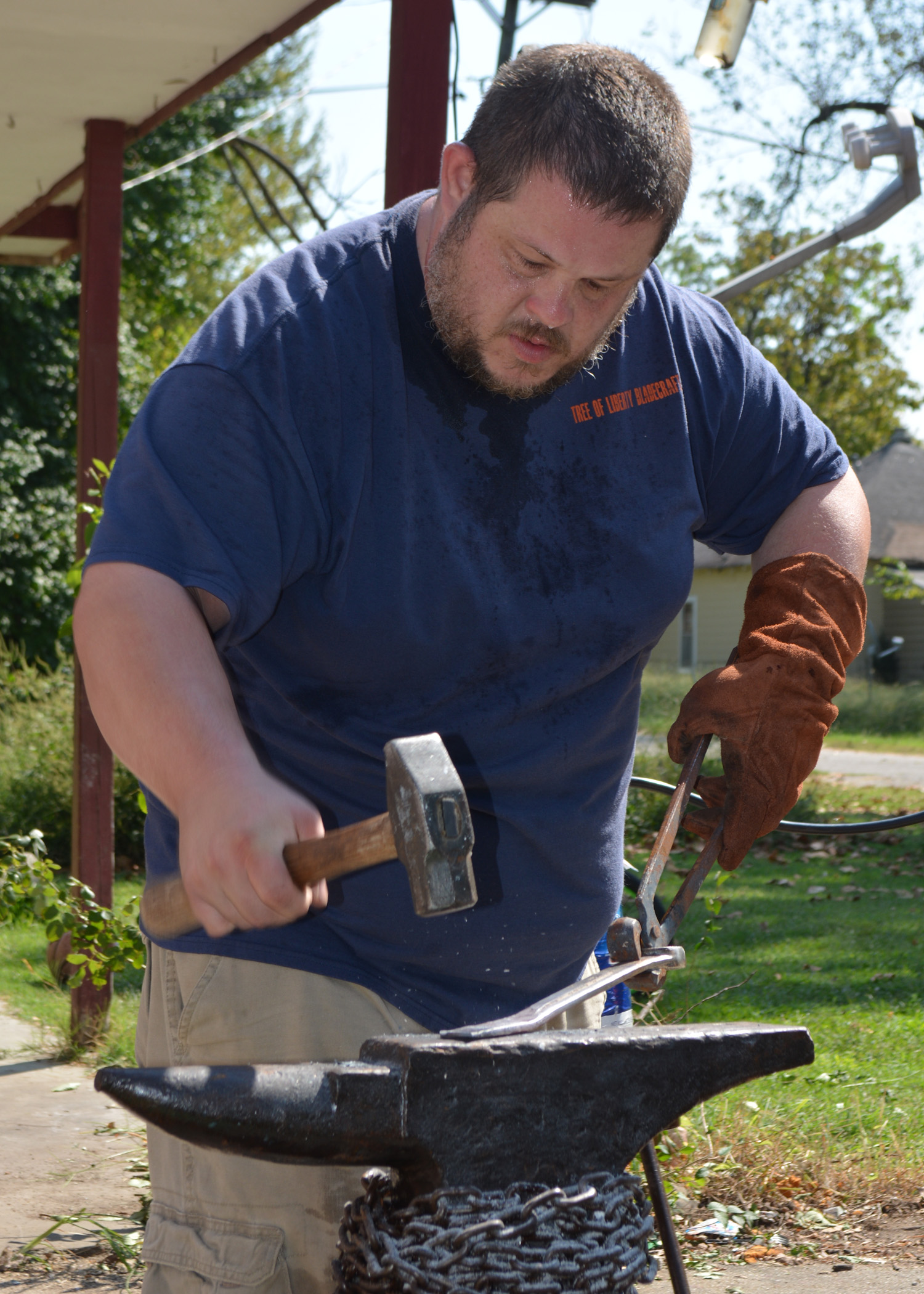 A man hammers a metal item on an anvil.