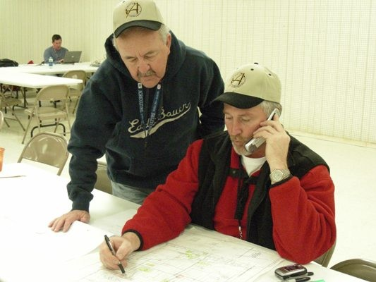 Two men looking at map while one talks on the phone