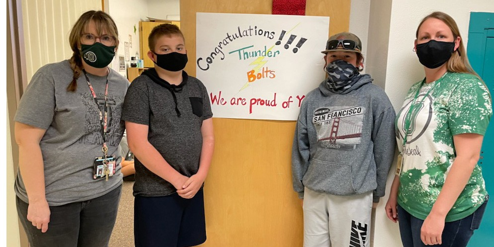 Four people wearing masks stand in front of an open door with a sign. Sign says Congratulations!!! Thunder Bolts. We are proud of you.